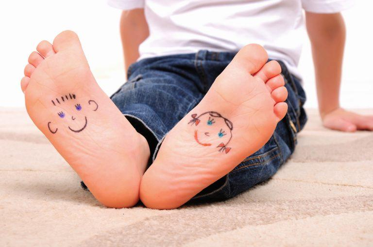 small,faces,painted,on,the,soles,of,a,young,boy